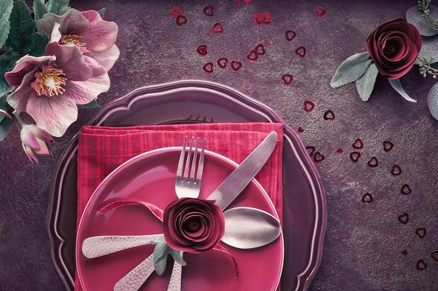 Plat met bordeauxrode borden en servies versierd met rozen en anemonen