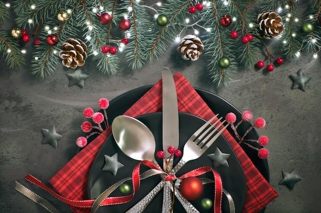 Plat met kerstdecoraties in groen en rood met berijpte bessen, snuisterijen, borden en servies