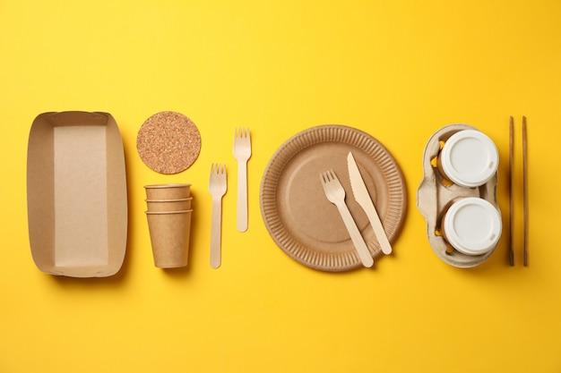 Plat met milieuvriendelijk servies op geel, ruimte voor tekst
