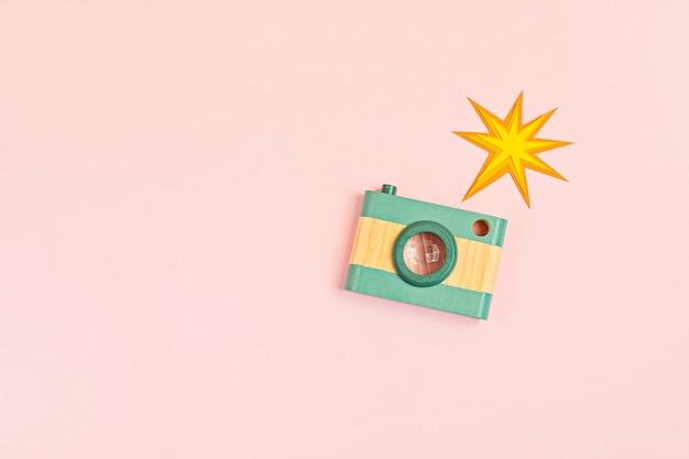 Plat met speelgoed houten camera en flitser op roze muur. social media, posts, likes, volgers, online fotografie klassen concept. bovenaanzicht, kopieer ruimte.