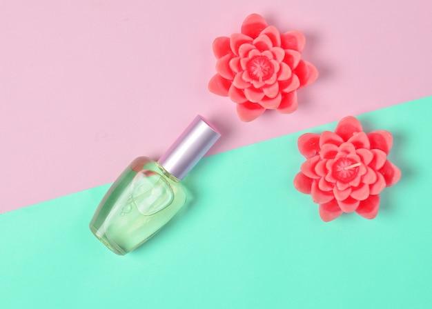 Plat minimalisme van een parfumfles en kaarsen in de vorm van bloemen op een pastel.