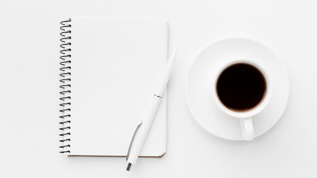 Plat notitieboekje en koffie arrangement