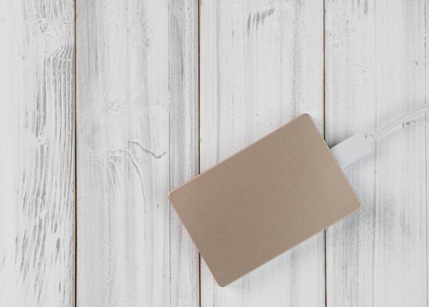 Plat ontwerp bronzen kleur externe harde schijf op witte houten tafel