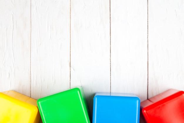 Plat op houten achtergrond. plastic blokjes voor kinderen.