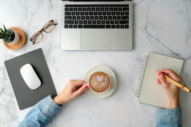 Plat opgestelde werkruimte. vrouwenhand met koffiekop, smartphone, computer, notitieboekje, ontwerper en stationair