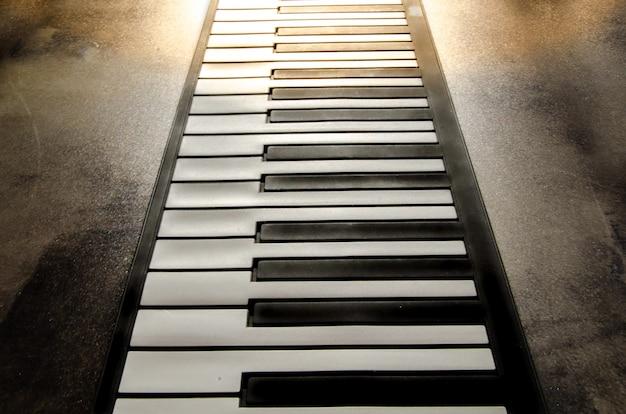 Plat pianotoetsenbord. pianotoetsen op gestructureerde achtergrond. zachte toning. warm zacht licht jazz muziek stal
