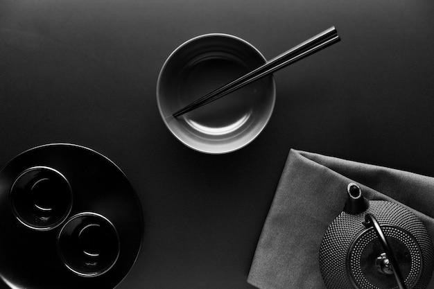 Plat serviesgoed met theepot en eetstokjes