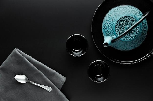 Plat serviesgoed met theepot en zilveren lepel
