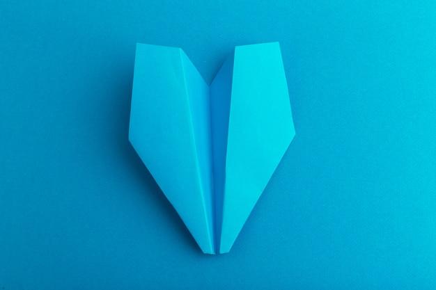 Plat van een papieren vliegtuig op pastelblauwe kleur