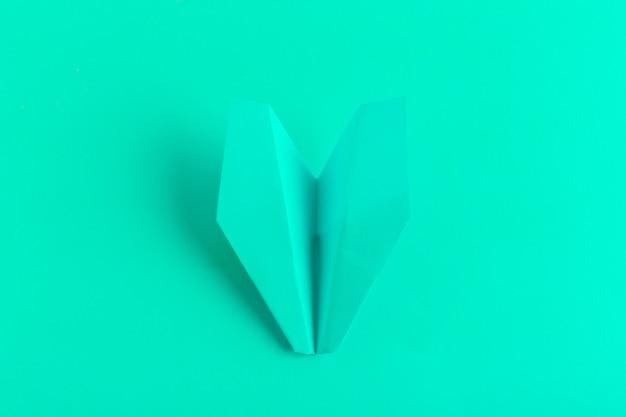 Plat van een papieren vliegtuigje op groene pastel kleuren achtergrond