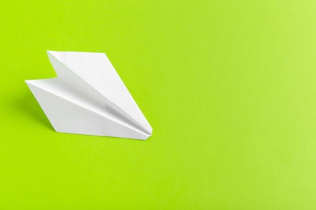 Plat van een papieren vliegtuigje op groene pastelkleur