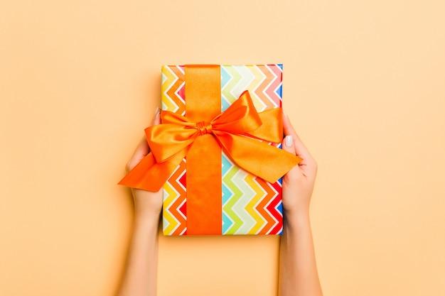 Plat van vrouw handen houden geschenk verpakt en versierd met strik op goud
