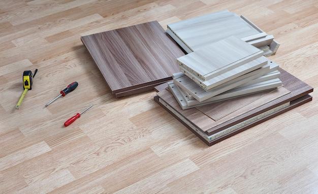 Plat verpakte meubels die thuis op de vloer liggen naast gereedschap voor montage.