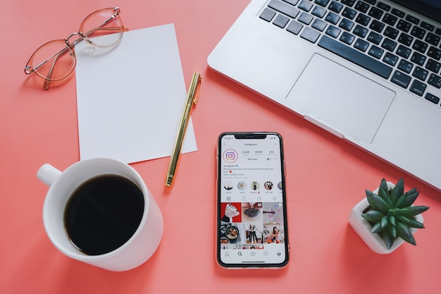 Plat werkruimte bureau en mobiele telefoon met een applicatie op het scherm met laptop en koffie achtergrond.