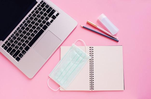 Plat werkruimte bureau met laptop, blanco notebook, medische maskers en alcohol gel op fel roze