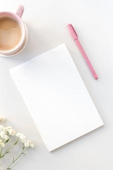 Plat werkruimtebureau met open notitieboekje, roze pen, koffie en gipskruidbloemen