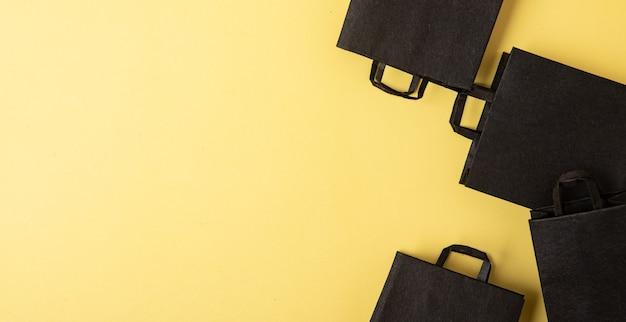 Plat zwarte boodschappentassen in black friday-uitverkoop op gele achtergrond met kopieerruimte