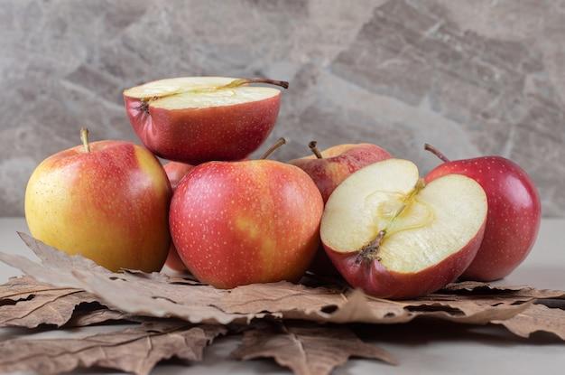 Plataan bladeren onder een bundel gesneden en hele appels op marmer