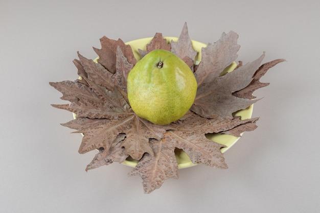 Plataan bladeren onder een enkele peer op een schaal op marmer