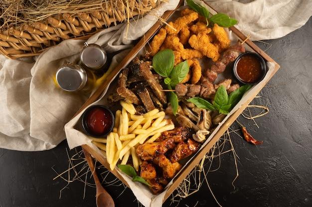 Plateau met frites, kipnuggets, rogge knoflookcroutons, varkensoren, kippenpoten, kebab en ketchup