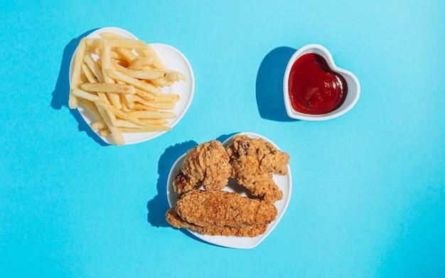 Platen in de vorm van een hart met snacks op een blauwe achtergrond, nuggets, vleugels, strips en friet met ketchup zonlicht harde schaduwen
