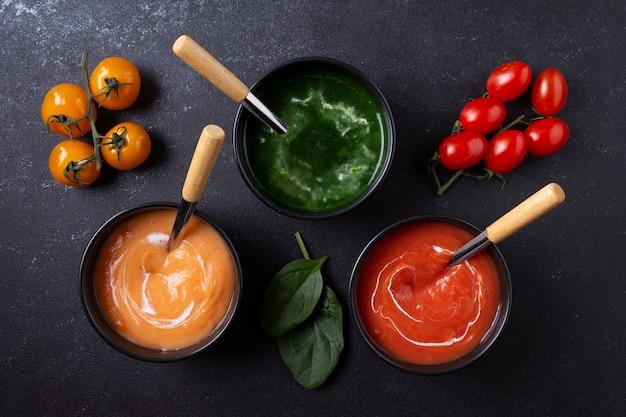 Platen van vegetarische soepen tomaat wortel spinazie zwarte achtergrond plat lag