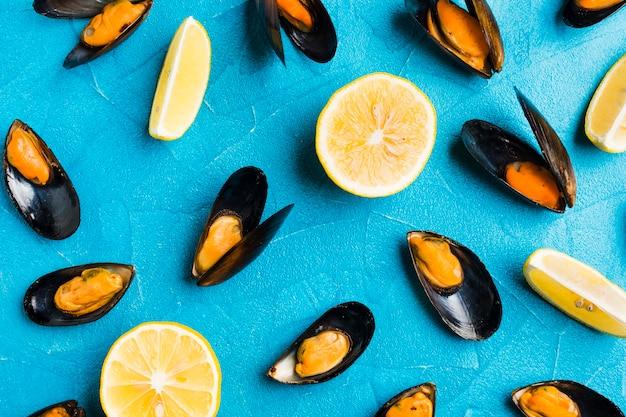 Platgelegde gekookte mosselen en schijfjes citroen verspreid over tafelblad