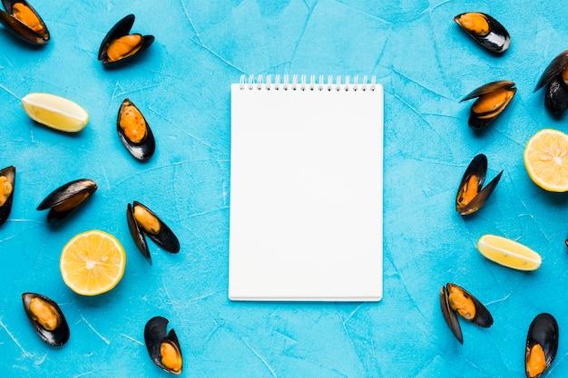 Platgelegde gekookte mosselen met notitieboekje