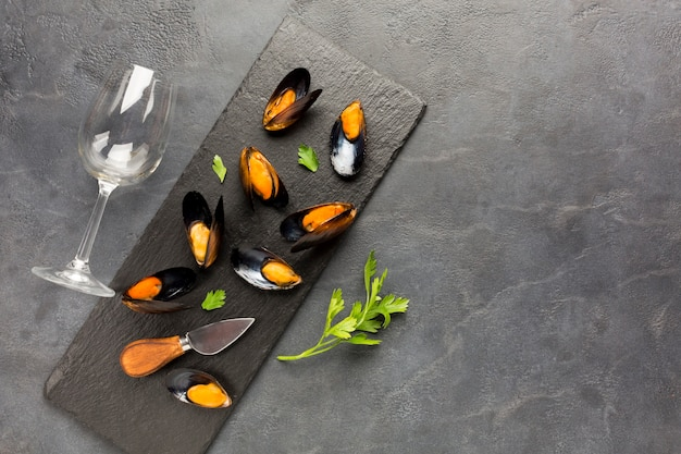 Platgelegde gekookte mosselen op leisteen met copyspace