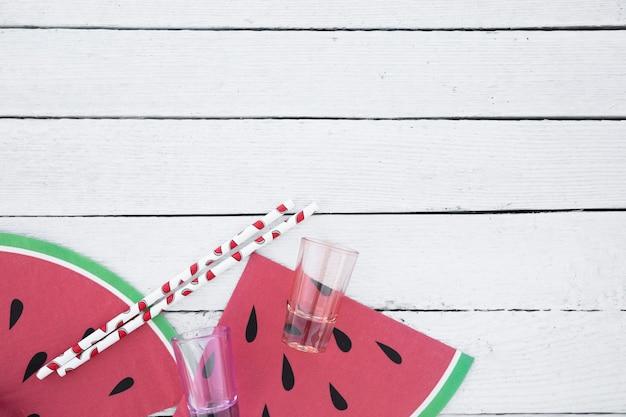 Platgelegde glazen en rietjes met watermeloenschijfjes