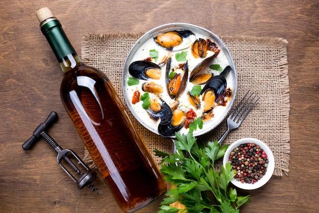 Platgelegde mosselen in witte saus en wijnfles