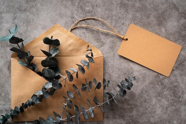 Platliggend arrangement met envelop en takje