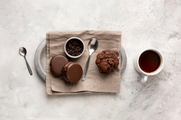 Platliggend arrangement met smakelijke muffin en koekjes