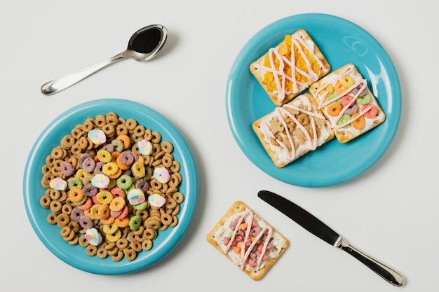 Platliggend arrangement met taartjes en ontbijtgranen op borden