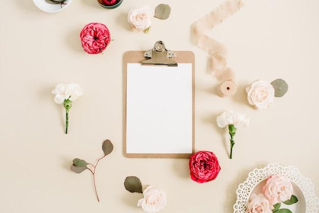 Platliggend bloemenframe met leeg klembord, rode en beige roze bloemknoppen, witte anjer, eucalyptus, lint op lichtbeige pastelachtergrond. bovenaanzicht