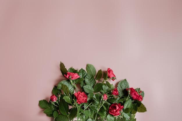 Platliggend bloemstuk met verse rode rozen op roze muur