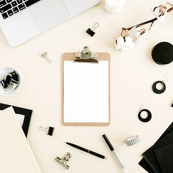 Platliggend bureau aan huis. werkruimte met klembord, laptop op pastelbeige achtergrond. bovenaanzicht