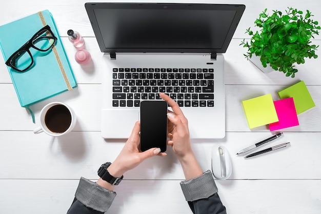 Platliggend bureau met bovenaanzicht. werkruimte met meisjeshanden, laptop, groene bloem in een pot, muntagenda, koffiemok op witte achtergrond.
