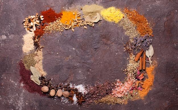 Platliggend compositiekader van verschillende kruiden over bruine leisteenachtergrond, bovenaanzicht