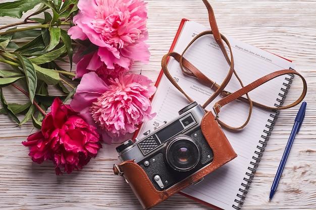 Platliggend damesbureau vrouwelijke werkruimte met laptop roze pioenrozen boeket camera en koffie op w...