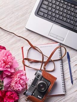 Platliggend damesbureau. vrouwelijke werkruimte met laptop, roze pioenrozen boeket, camera en koffie op witte achtergrond. bovenaanzicht vrouwelijke achtergrond.