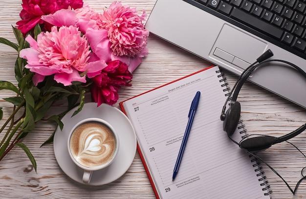 Platliggend damesbureau. vrouwelijke werkruimte met laptop, roze pioenrozen boeket en koffie op witte achtergrond. bovenaanzicht vrouwelijke achtergrond.