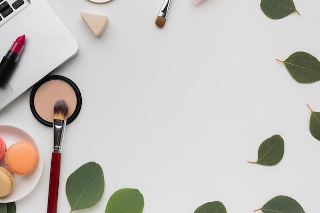 Platliggend rond frame met make-up en bladeren