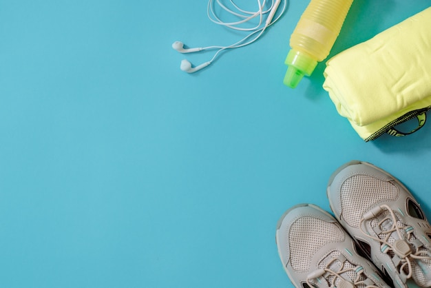 Platliggend schot van sportuitrusting. sneakers, halters, oortelefoons en telefoon op blauw