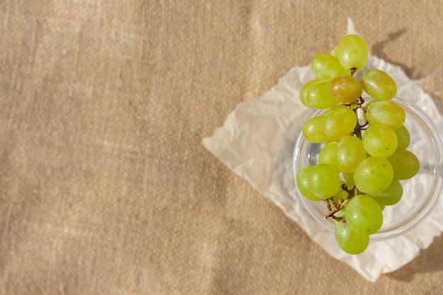 Platliggend stilleven en eten foto een schotel met een tros druiven staat op een jute