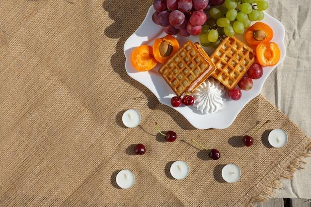 Platliggend stilleven en voedselfoto een bord met fruit en wafels staat op een jute