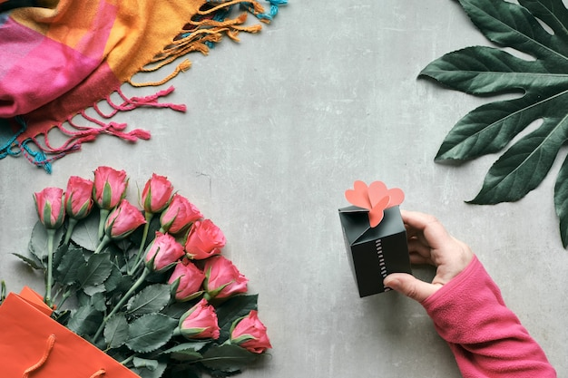 Platliggend, stilleven met bos roze bloemen en exotisch plantenblad. hand houdt kleine geschenkdoos met harten bovenop. bovenaanzicht op lichte steen. valentine, verjaardag of moederdagconcept.