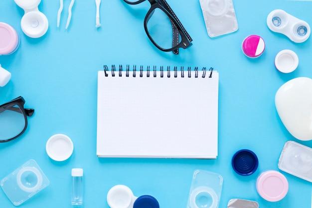 Platliggende bril en optische objecten met notebookmodel