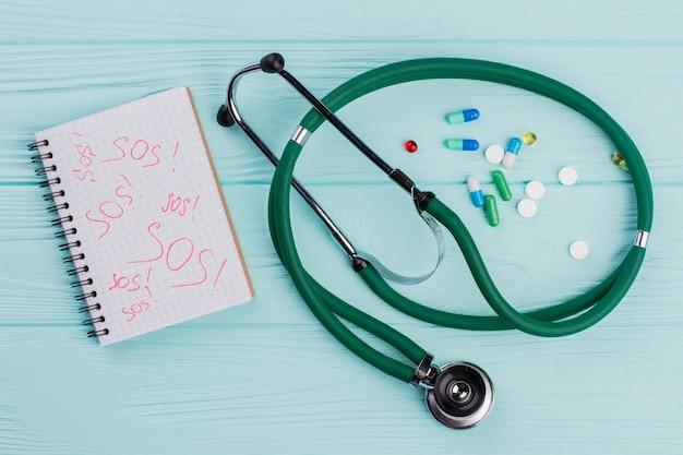 Platliggende capsules en stethoscoop op blauwe achtergrond. sos geschreven op kladblok.