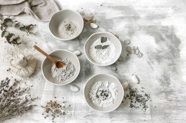 Platliggende compositie met de bereiding van een gezichtsmasker van klei, natuurlijke ingrediënten in cosmetologie.